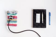 Стетоскоп, тетрадь на модель-макете взгляд сверху предпосылки стола офиса доктора ` s детей Стоковое Изображение RF