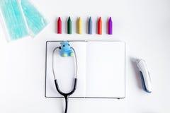 Стетоскоп, тетрадь на модель-макете взгляд сверху предпосылки стола офиса доктора ` s детей Стоковые Изображения
