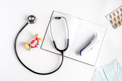 Стетоскоп, тетрадь на модель-макете взгляд сверху предпосылки стола офиса доктора ` s детей Стоковая Фотография
