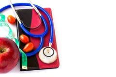 Стетоскоп Bule и красное яблоко, измеряя лента на белом backgr Стоковая Фотография RF