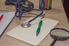Стетоскоп ` s доктора на таблице рабочее место доктора с стетоскопом на таблице Стоковое фото RF
