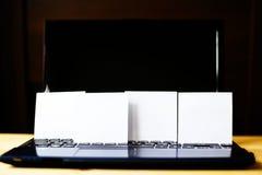 4 стикера белой бумаги стоя на ПК на деревянном столе Стоковое Фото