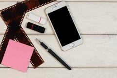 Стикеры, ручка, телефон, карточка флэш-память, крен камеры на деревянном столе Стоковые Изображения RF