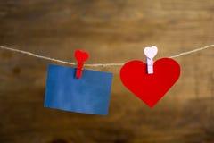 Стикер и меньшие остатки сердца на зажимке для белья на веревочке Стоковое Изображение
