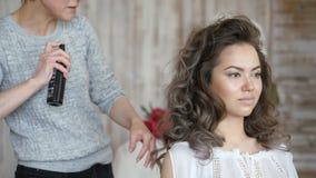 Стилизатор визажиста работает с моделью парикмахер делает дизайн волос модели стилизатор парикмахера фиксирует акции видеоматериалы