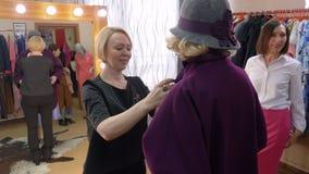 Стилизатор моды помогая выбрать новое пальто для зрелой женщины в бутике одежд Пальто старшей женщины пробуя в моде сток-видео