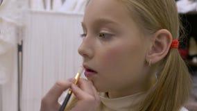 Стилизатор прикладывает макияж к предназначенной для подростков девушке сток-видео