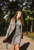 Стильная белокурая модель в платье knit и теплом пальто идя в Стоковые Фото