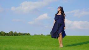 Стильная беременная женщина идя на зеленую траву к камере сток-видео