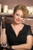Стильная блондинка в черном платье с ожерельем жемчуга Стоковое фото RF