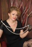 Стильная блондинка в черном платье с ожерельем жемчуга Стоковое Изображение RF