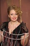 Стильная блондинка в черном платье с ожерельем жемчуга Стоковое Фото
