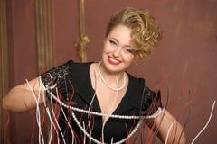 Стильная блондинка в черном платье с ожерельем жемчуга Стоковая Фотография