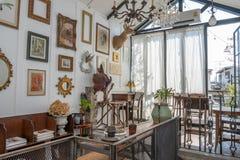 Стильная винтажная мебель в просторном плоском интерьере с деревянными стульями и рамка на стене стоковое фото rf