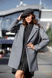 Стильная девушка брюнета одетая в модном сером платье, серой куртке и крышке представляет в улице города на солнечном стоковая фотография rf
