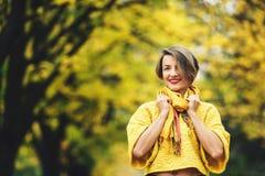 Стильная девушка в осени в желтых свитере и шарфе на предпосылке желтых кленов Стоковое Изображение RF