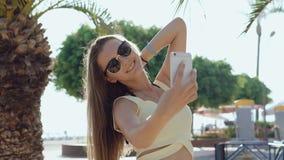 Стильная девушка используя мобильный телефон и принимающ selfie на улице в горячий летний день акции видеоматериалы