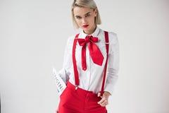 стильная девушка представляя в белой рубашке, красных подтяжках и смычке с деловой газетой, стоковые изображения
