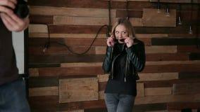 Стильная девушка представляя для фотографа в студии акции видеоматериалы