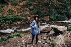 Стильная девушка путешественника в шляпе показывая палец на реке i водопада Стоковые Изображения