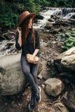 Стильная девушка путешественника в шляпе сидя на водопаде на реке в su Стоковое Фото