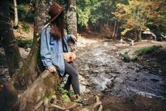 Стильная девушка путешественника в шляпе сидя на дереве и смотря rive Стоковая Фотография