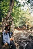 Стильная девушка путешественника в шляпе сидя на дереве и смотря rive Стоковое Изображение RF