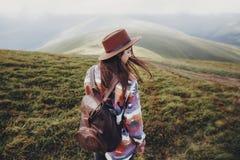 Стильная девушка путешественника в шляпе с рюкзаком идя в горы Стоковое фото RF