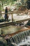 Стильная девушка путешественника с шляпой идя на реку водопада в солнце Стоковая Фотография RF