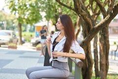 Стильная девушка сидя на стенде внутри городском, держащ модные eyeglasses стоковые изображения
