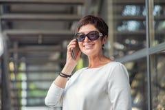 Стильная достигшая возраста женщина говоря по телефону на улице стоковые фото