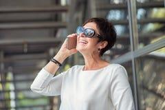 Стильная достигшая возраста женщина говоря по телефону на улице стоковое фото rf
