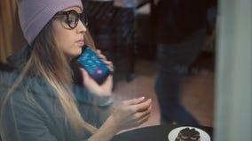 Стильная женщина битника в стеклах используя умный вахту и говорить на кофе телефона выпивая в кафе акции видеоматериалы