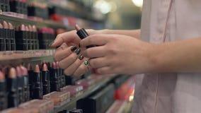 Стильная женщина выбирает декоративные косметики для губ для яркого макияжа и прикладывает губную помаду испытывая в наличии на м акции видеоматериалы
