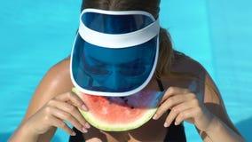 Стильная женщина в бассейне есть кусок арбуза и усмехаясь, имеющ закуску акции видеоматериалы