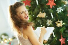 Стильная женщина около сочинительства рождественской елки в тетради стоковое фото