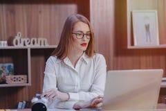 Стильная женщина работает на столе ноутбука в современном офисе стоковая фотография