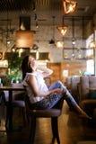 Стильная женщина сидя на кафе с ногами дальше подпирает стула, носящ этнические джинсы Стоковые Изображения