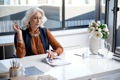 Стильная задумчивая женщина смотрит кассету Стоковое Изображение RF