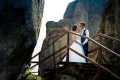 Стильная как раз пожененная пара нежно держит руки пока стоящ на деревянных лестницах между 2 утесами солнечно Стоковые Изображения RF
