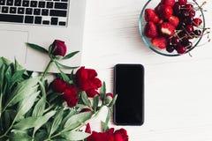 Стильная компьтер-книжка с телефоном, клубниками и вишнями и beautif Стоковые Изображения