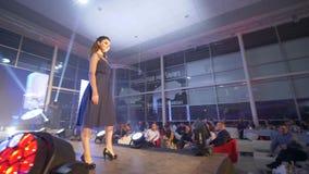 Стильная модель подиума в высоких пятках в выравнивать черное дефиле платья на подиуме на модном параде в прожектор видеоматериал