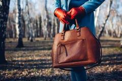 : Стильная модная женщина нося яркое платье держа коричневую сумку сумки стоковое изображение rf