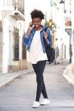 Стильная молодая женщина идя вниз с улицы с умным телефоном Стоковая Фотография RF