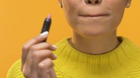 Стильная молодая женщина прикладывая обнаженную губную помаду и усмехаясь в камеру, косметики акции видеоматериалы