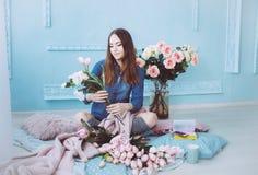 Стильная молодая женщина сидя на поле, делая букет цветка розовых тюльпанов в светлой sunlit комнате с голубыми стенами стоковое изображение rf