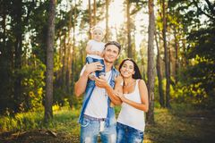 Стильная молодая семья блондинкы мамы, папы и дочери одного годовалой сидя около отца на плечах, outdoors вне города в a Стоковые Фотографии RF