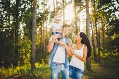 Стильная молодая семья блондинкы мамы, папы и дочери одного годовалой сидя около отца на плечах, outdoors вне города в a Стоковое Изображение RF