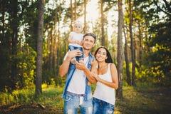 Стильная молодая семья блондинкы мамы, папы и дочери одного годовалой сидя около отца на плечах, outdoors вне города в a Стоковое фото RF