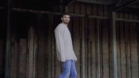 Стильная мужская модель идет и смотрит в сторону на катакомбах 4K видеоматериал